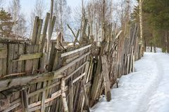 Ragged old wooden fence. With barbed wire. path in the snow along the rural fence. non urban winter landscape stock photos