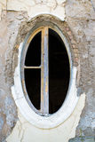 Ragged oval window in an old building Stock Photos
