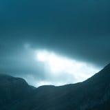 Raggi di luce drammatici che spingono verso l'alto attraverso le nuvole Immagine Stock