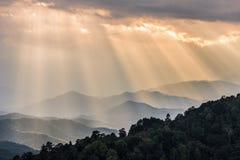 Raggi di sole arancio che splendono attraverso il cielo nuvoloso alla catena montuosa Fotografie Stock Libere da Diritti