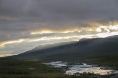 Raggi di sole che si formano sopra le montagne sul tramonto che dà bella luce dorata sopra il fiume in Sarek, Svezia Immagini Stock Libere da Diritti