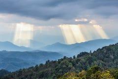 Raggi di sole che splendono attraverso il cielo nuvoloso alle montagne blu Fotografia Stock Libera da Diritti