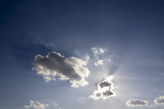 Raggi di sole e nuvole sugli ambiti di provenienza grigi del cielo Immagine Stock