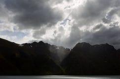 Raggi di Sun che scoppiano attraverso le nuvole spesse Fotografia Stock