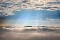 Raggi di Sun sopra le nubi immagine stock libera da diritti