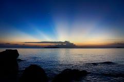 Raggi di Sun sulla spiaggia al tramonto Immagini Stock Libere da Diritti