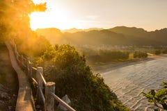 Raggi dorati del sole sull'orizzonte della montagna in cima ad un vecchio alon del percorso Fotografia Stock Libera da Diritti
