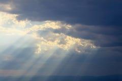 Raggi luminosi che scorrono sopra la catena montuosa Immagine Stock