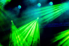 Raggi luminosi di luce verde dal riflettore attraverso il fumo al teatro o alla sala da concerto Materiale di illuminazione per u fotografia stock