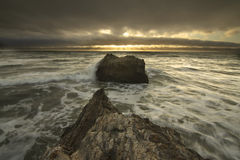 Raggi luminosi sopra le onde di oceano che spruzzano sulle rocce Fotografia Stock