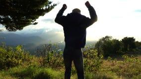 Raggiungimento della parte superiore Il salto dell'uomo felice e sollevare sulle mani sul bello lanscape della montagna sull'alba video d archivio