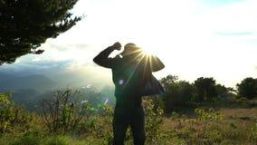 Raggiungimento della parte superiore Il salto dell'uomo felice e sollevare sulle mani sul bello lanscape della montagna sull'alba stock footage