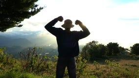 Raggiungimento della parte superiore L'uomo solleva sulle mani sul bello lanscape della montagna sull'alba Feelling felice, sente stock footage