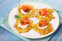 Raggmunkar med laxen Grönsakstruvor med fisken Latkes på en platta royaltyfria bilder