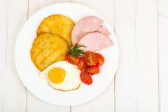 Raggmunkar stekt ägg, korv för frukost royaltyfri foto