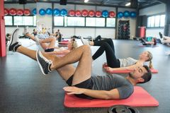 Raggruppi gli adulti sulle loro parti posteriori che fanno l'allungamento del muscolo Fotografia Stock