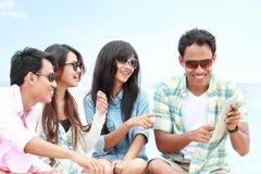 Raggruppi gli amici che godono della festa della spiaggia insieme al pc della compressa Fotografie Stock
