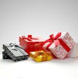Raggruppi i contenitori di regalo con l'arco con fondo grigio Fotografia Stock