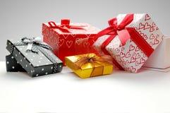 Raggruppi i contenitori di regalo con l'arco con la parte anteriore grigia del fondo Fotografia Stock