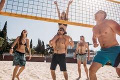 Raggruppi i giovani amici caucasici che giocano la pallavolo sulla spiaggia sulle vacanze estive immagini stock libere da diritti