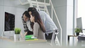 Raggruppi i giovani colleghe che discutono insieme il progetto creativo durante i colleghi moderni di processo del lavoro nel fun archivi video