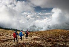 Raggruppi i turisti con gli zainhi che camminano giù sul dur della traccia di montagna Fotografia Stock Libera da Diritti
