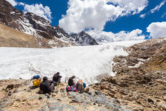 Raggruppi il cibo di riposo di seduta del ghiacciaio delle montagne della gente, viaggio della Bolivia Fotografie Stock Libere da Diritti