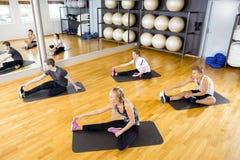 Raggruppi l'allungamento degli esercizi per la flessibilità del muscolo al centro di forma fisica Fotografie Stock