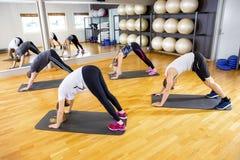 Raggruppi l'esercitazione la flessibilità e dell'equilibrio del corpo alla palestra di forma fisica Fotografia Stock Libera da Diritti