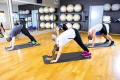 Raggruppi l'esercitazione la flessibilità e dell'equilibrio del corpo alla palestra di forma fisica Immagini Stock