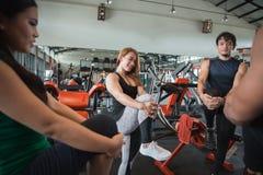 Raggruppi l'uomo e la donna che fanno insieme l'allungamento delle gambe Fotografia Stock