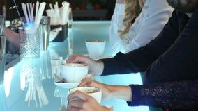 Raggruppi la gente di affari che chiacchiera e che beve il caffè in una barra Immagini Stock