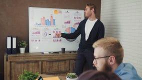 Raggruppi la gente di affari che ha una riunione facendo uso di un bordo bianco nello spazio ufficio moderno video d archivio