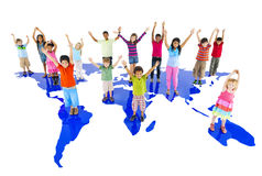 Raggruppi le mani dei bambini su che stanno il concetto della mappa di mondo Fotografia Stock