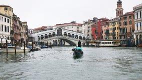 Raghetti boat and Rialto Bridge in Venice in rain Royalty Free Stock Image