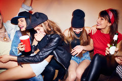 Raging Fun at Late Night Party. Group of several young people getting drunk at underground swag party, one girl  almost choking on beer as all suddenly burst out Royalty Free Stock Images