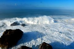 Raging ocean water with rocks and foam royalty free stock images