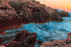 Raging ocean waves breaking on rocks at sunset Stock Images
