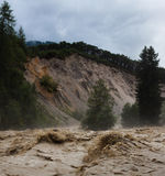 Raging Rapids. A river in flood in the European Alps, with a  large erosion slope Stock Image