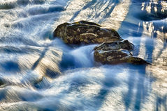 Raging river flows around rocks Royalty Free Stock Image