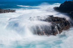 Raging sea flows over lave rocks on shore line Stock Image