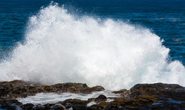 Raging sea flows over lave rocks on shore line Royalty Free Stock Images