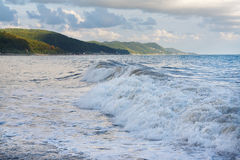 Raging sea waves on the beach against the cloudy sky after storm Royalty Free Stock Images