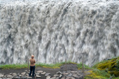 Raging waterfalls. The tourist looks at big raging falls Royalty Free Stock Photos