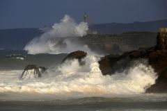 Raging waves on the Cantabrian Sea coast. Raging waves breaking against Mouro's Island lighthouse and the Cantabrian Sea coast (Santander, Spain royalty free stock images