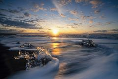 Raging waves smashing ice blocks at sunrise on Diamond Beach. The Diamond Beach is a strip of black sand belonging to the greater Breiðamerkursandur glacial stock image