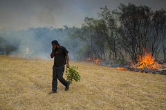 Raging wildfire in Port Elizabeth, South Africa. Adults and children keeping a wildfire under control that is raging near a home for destitute adults and a Royalty Free Stock Photo