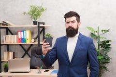 Ragioni per le quali dovreste bere il caffè sul lavoro Tazza di caffè barbuta della tenuta dell'uomo d'affari del responsabile de immagine stock