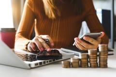 Ragioniere che lavora allo scrittorio in ufficio facendo uso del calcolatore e dello smartphone per calcolare bilancio immagine stock