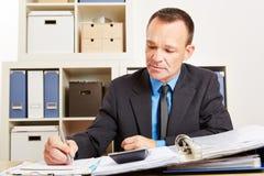 Ragioniere durante la verifica di imposta in ufficio fotografie stock